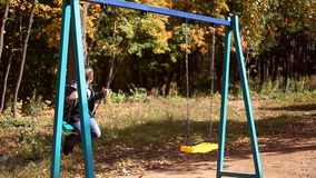 Boy and girl singing on swings. In the park stock footage