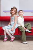Boy and girl sit back to back Royalty Free Stock Photo