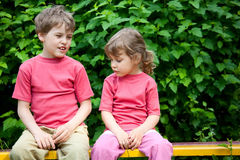The boy and the girl sit on a bench in park Stock Photography