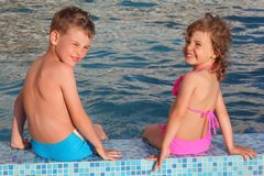 Boy and girl sit on border of pool. Summer Stock Image