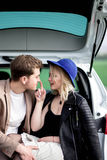 The boy and the girl sit on a car trunk. And laughing Royalty Free Stock Photography