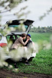 The boy and the girl sit on a car trunk and laughing. The boy and the girl sit on a car trunk Royalty Free Stock Photo
