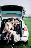 The boy and the girl sit on a car trunk and laughing. The boy and the girl sit on a car trunk Royalty Free Stock Images