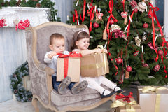 Boy and the girl sit in a chair. With gifts near a Christmas fir-tree Stock Photography