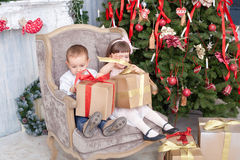 Boy and the girl sit in a chair Stock Image