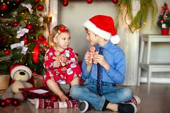 Boy and girl sit on the floor under the Christmas tree. children eat ginger man. Next to the gifts. They are writing. Beautiful happy laughing children in New Stock Photos