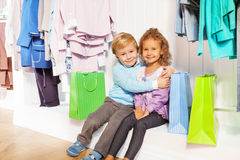Boy and girl sit hugging under hangers in shop Royalty Free Stock Photography
