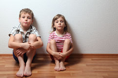 Boy and girl sit leaning on wall Royalty Free Stock Images