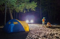 Boy and girl sit at night tourists tent. Royalty Free Stock Photography