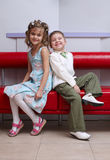 Boy and girl sit o coach. Boy and girl sit back to back on the couch Stock Image