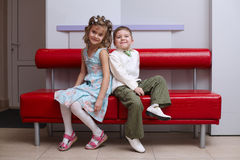 Boy and girl sit o coach. Boy and girl sit back to back on the couch Royalty Free Stock Photo