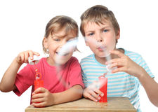 Boy and girl sit at table and blow bubbles Stock Image
