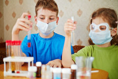 Boy and girl sit at table with chemical reagents Royalty Free Stock Photos
