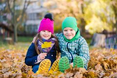 Boy and girl sit during walk in autumn park. Boy and girl sit during walk in autumn rainy park royalty free stock images