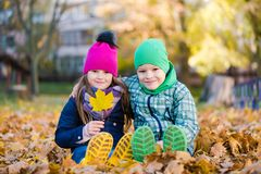 Boy and girl sit during walk in autumn park. Boy and girl sit during walk in autumn rainy park royalty free stock photography