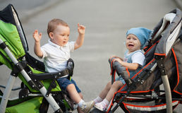 Boy and girl sitting in baby carriages Stock Image