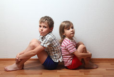 Boy and girl sitting back to back. Thoughtful boy and girl in home clothes sitting back to back Royalty Free Stock Photo