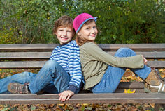 Boy and girl sitting on a bench Royalty Free Stock Photos