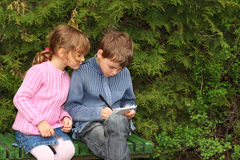 Boy and girl sitting on bench near trees Stock Photos