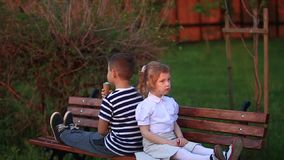 Boy and girl are sitting on the bench. Run around the park and blow dandelions stock footage