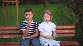 Boy and girl are sitting on the bench. Run around the park and blow dandelions stock video footage