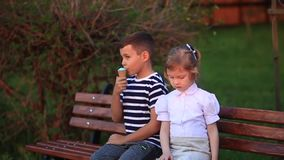 Boy and girl are sitting on the bench. Run around the park and blow dandelions. Summer sunset stock video