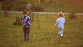 Boy and girl are sitting on the bench. Run around the park and blow dandelions stock video
