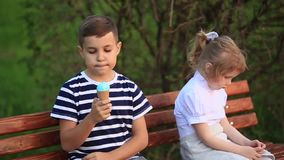 Boy and girl are sitting on the bench. Run around the park and blow dandelions. Summer sunset stock footage