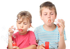 Boy and girl sitting and blowing bubbles Stock Photos