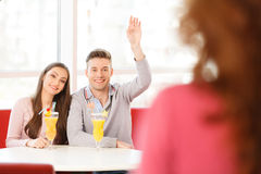 Boy and girl sitting in cafe and drinking juice. Stock Photography