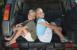 Boy and girl (9-11) sitting in car boot, back to back, smiling, side view, portrait Stock Photo