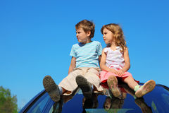 Boy and girl sitting on car roof on sky Stock Photo