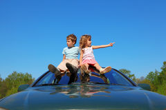 Boy and girl sitting on car roof on sky Stock Images