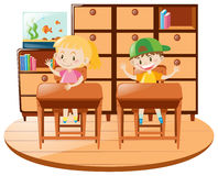Boy and girl sitting on desk in the classroom Royalty Free Stock Image