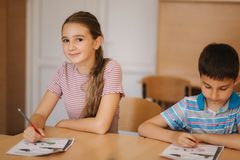 Boy and girl sitting at desk and writing a text.  royalty free stock photos