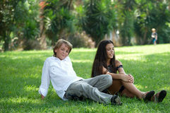 Boy and girl sitting on the grass. Pre-teen boy and girl in a bright sunny summer day sitting on the grass in the park royalty free stock images