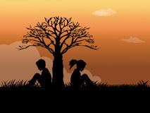 Boy and girl sitting on the grass. Silhouette of boy and girl sitting on the grass Stock Photo