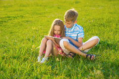 Boy with  girl sitting on the lawn. Royalty Free Stock Photo