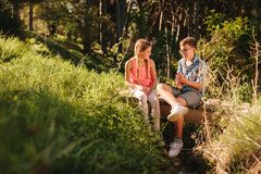 Kids in love sitting in a park and talking. Boy and girl sitting on a log bridge in a park and talking. Kids spending time talking to each other sitting in a royalty free stock images