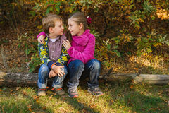 Boy and girl sitting and looking Royalty Free Stock Photo