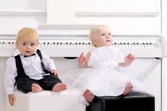 Boy and girl sitting near piano Stock Photo