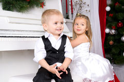 Boy and girl sitting near white piano. Boy and girl in concert dress sitting near the white piano Stock Photos