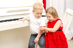 Boy with girl sitting near white piano. In bright room Stock Photo