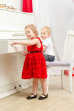 Boy with girl sitting near white piano. In bright room Royalty Free Stock Image