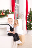 Boy and girl sitting near white piano. Boy and girl in concert dress sitting near the white piano Royalty Free Stock Photos