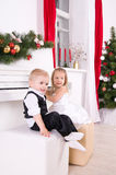 Boy and girl sitting near white piano. Boy and girl in concert dress sitting near the white piano Royalty Free Stock Photography