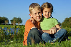 Boy and girl sitting outside Royalty Free Stock Photos