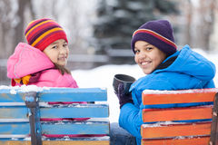 Boy and girl sitting in park on bench. Stock Image