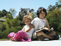 Boy (10-12) and girl (6-8) sitting in park, boy with skateboard in lap, smiling, portrait Stock Photography