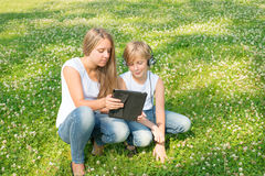 Boy and girl sitting in the park and enjoy a digital tablet Royalty Free Stock Photography